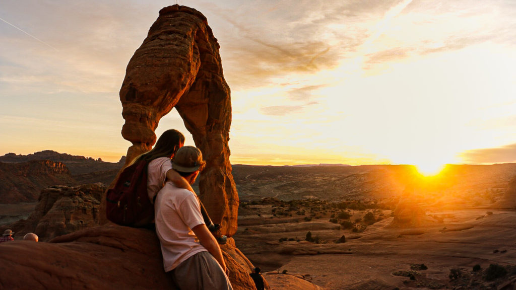 Briana and Billy by the delicate arch at sunset in arches national park
