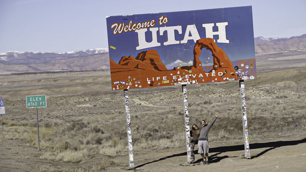 Briana and Billy standing under the welcome to Utah sign