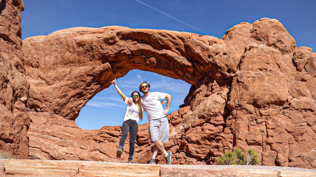 Briana and Billy infront of the windows rock formation in arches national park
