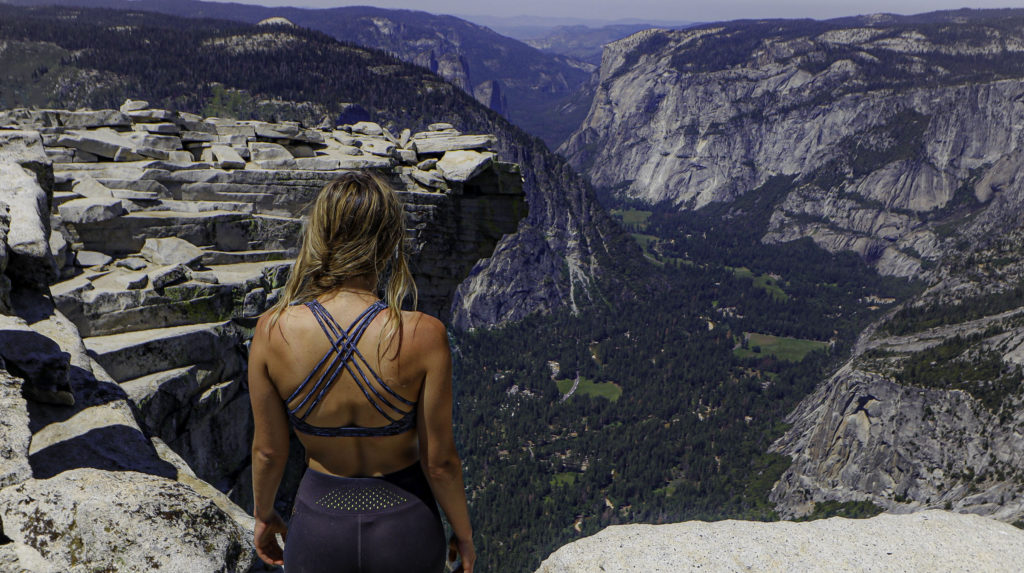 Briana, with her back facing the camera, standing on the top of half dome.  Overlooking the grand view.